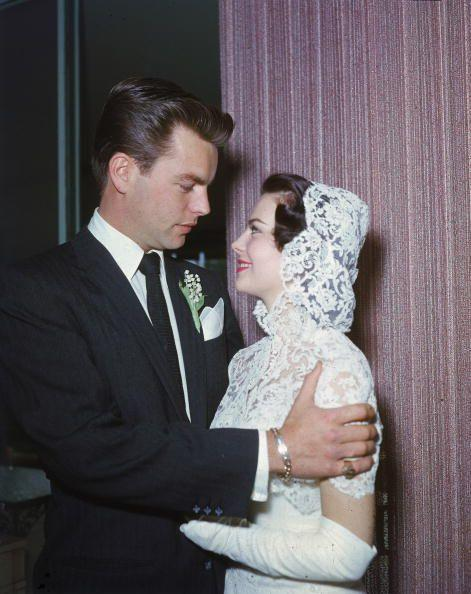 """<p>Robert Wagner and Natalie Wood were Hollywood's """"It"""" couple in the '50s. The actor proposed by placing a <a href=""""https://www.biography.com/news/natalie-wood-robert-wagner-relationship#:~:text=Wagner%2C%20known%20to%20friends%20and,Hollywood%20by%20the%20mid%2D1950s.&text=The%20attraction%20was%20real%20and,ring%20in%20Wood's%20champagne%20glass."""" rel=""""nofollow noopener"""" target=""""_blank"""" data-ylk=""""slk:pearl and diamond engagement ring"""" class=""""link rapid-noclick-resp"""">pearl and diamond engagement ring</a> in a glass of champagne. They got married in Scottsdale, Arizona in 1957, divorced in 1962, and famously remarried a decade later.</p>"""