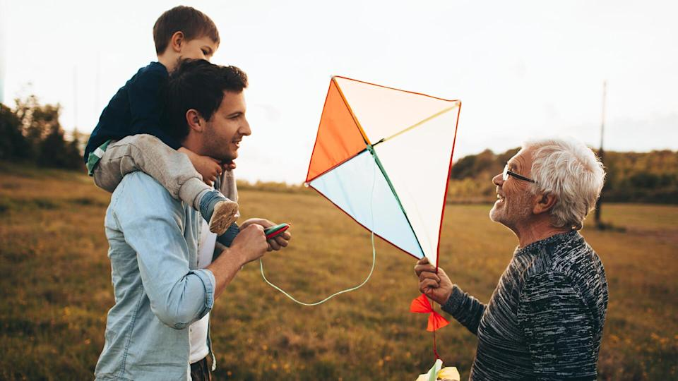 Photo of a three generations of men, who enjoy kite running and spending time together outdoors in the nature.