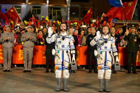 Chinese astronauts Jing Haipeng (R), Chen Dong wave before the launch of Shenzhou-11 manned spacecraft, in Jiuquan, China, October 17, 2016. China Daily/via REUTERS