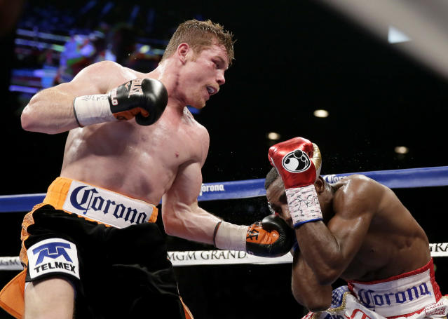 Canelo Alvarez, left, of Mexico, hits Erislandy Lara, of Cuba, during their super welterweight fight, Saturday, July 12, 2014, in Las Vegas. (AP Photo/John Locher)