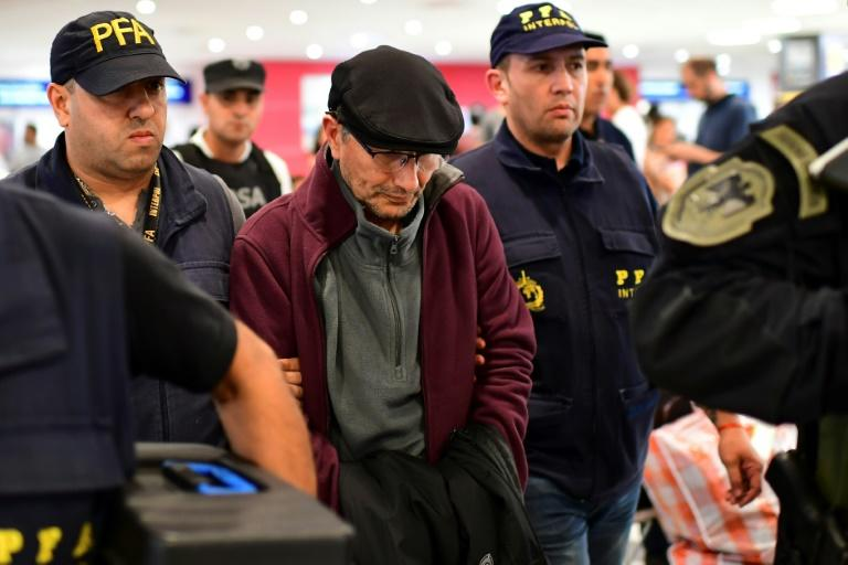 "Mario Sandoval (C) is escorted by police officers at Buenos Aires' Ezeiza airport after being extradited from France to face trial over the 1976 disappearance of a student during Argentina's ""dirty war"""