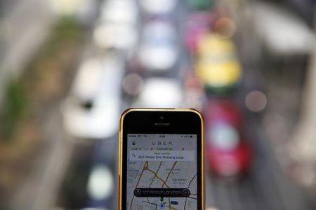 A phone running the Uber application is held above the traffic in central Bangkok