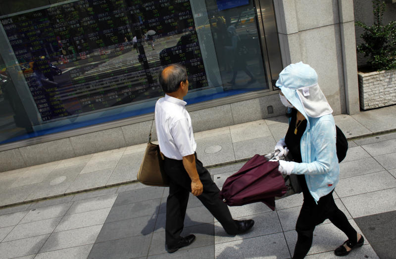 People stroll outside a securities firm in Tokyo, Friday, Aug. 30, 2013. Japan's economic recovery gained momentum in July, as manufacturing accelerated and consumer prices rose for a second straight month, despite weaker household spending and retail sales. (AP Photo/Junji Kurokawa)