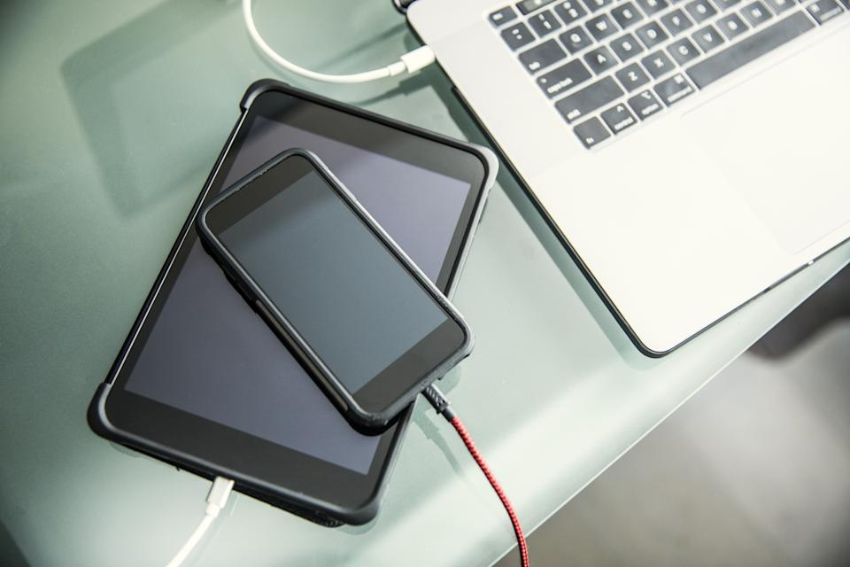 Mobile devices and laptop charging on office desk (Photo: Getty Images)