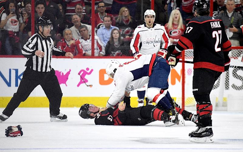 Alex Ovechkin leans over Andrei Svechnikov after their fight in Monday's clash between the Carolina Hurricanes and the Washington Capitals
