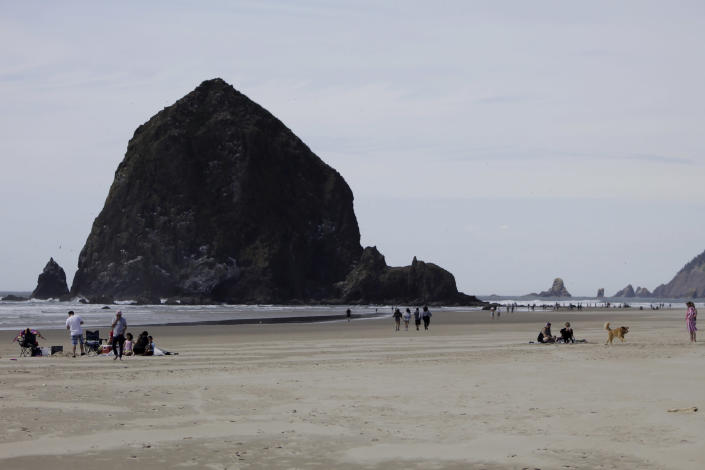 This Thursday, May 28, 2020, photo shows people visiting a beach in front of Haystock Rock during the coronavirus outbreak in Cannon Beach, Ore. With summer looming, Cannon Beach and thousands of other small, tourist-dependent towns nationwide are struggling to balance fears of contagion with their economic survival in what could be a make-or-break summer. (AP Photo/Gillian Flaccus)
