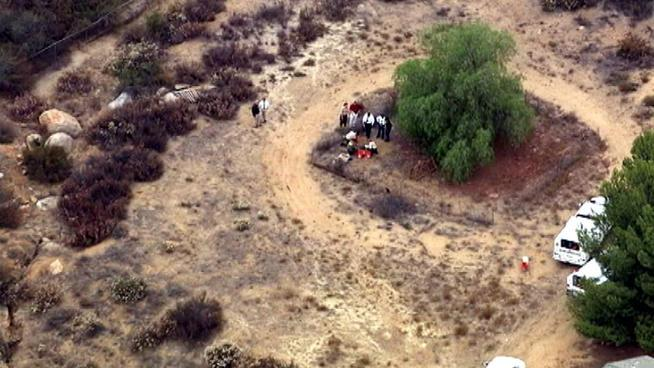 This video frame grab released courtesy of NBCLA.com shows an aerial view of investigators digging behind a Menifee, Calif., property in the search for 11-year-old Terry Smith on Wednesday July 10, 2013. Authorities say they've found possible human remains at the Southern California home of Smith an autistic boy who vanished over the weekend. (AP Photo/NBCLA.com) MANDATORY CREDIT NBCLA