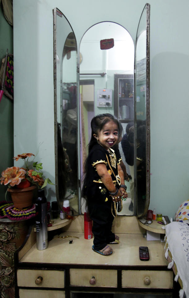 Indian Jyoti Amge, 18, who stands at 61.95 centimeters (2 feet), poses in front of a mirror as she prepares for a press conference with Guinness World Records at her home in Nagpur, India, Friday, Dec. 16, 2011. Officials from Guinness were expected to measure Amge later Friday and declare her the World's Shortest Woman. (AP Photo/Manish Swarup)