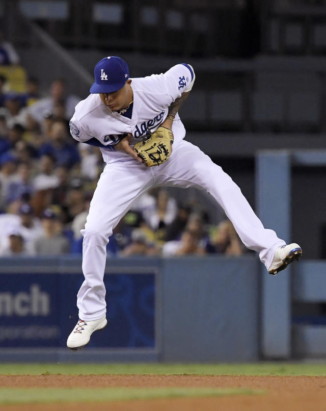 Los Angeles Dodgers shortstop Manny Machado fields a ball hit by San Francisco Giants' Buster Posey during the fourth inning of a baseball game Wednesday, Aug. 15, 2018, in Los Angeles. Posey was thrown out at first on the play. (AP Photo/Mark J. Terrill)