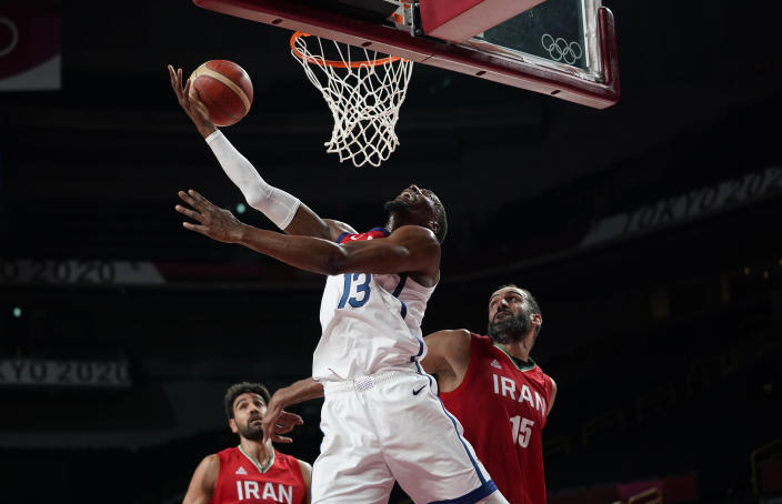 United States' Bam Adebayo (13), center, drives to the basket over Iran's Hamed Haddadi (15), right, during men's basketball preliminary round game at the 2020 Summer Olympics, Wednesday, July 28, 2021, in Saitama, Japan. (AP Photo/Charlie Neibergall)