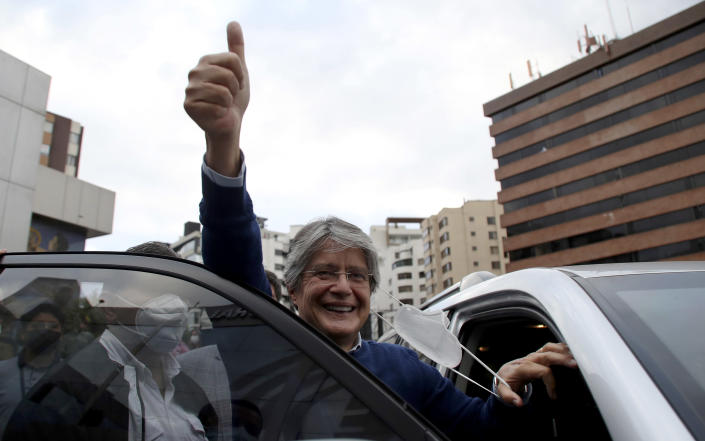 Presidential candidate Guillermo Lasso, representing the Creating Opportunities party or CREO, flashes a thumbs up after attending an event with rival Yaku Perez, of the Pachakutik political party, in which both are asking for a ballot recount of Sunday's election, in Quito, Ecuador, Friday, Feb. 12, 2021. It remains undecided which of the two has the votes to advance to the run-off race in April to face frontrunner Andres Arauz. (AP Photo/Dolores Ochoa)