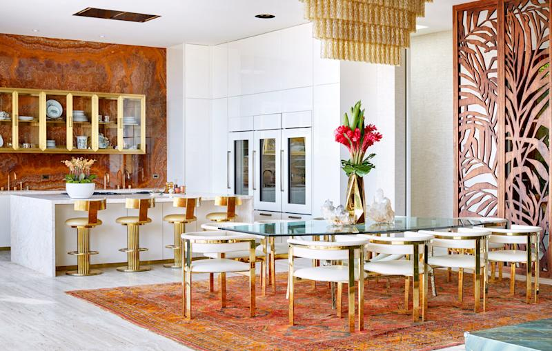 In the open-plan kitchen and dining area, a custom hand-blown amber-glass light fixture hangs above a 1950s handcrafted table from Paris and an antique Oushak rug. The kitchen appliances are by Gaggenau, the refrigerators are by Sub-Zero, and the floors throughout are Italian travertine. The china on display in the kitchen cabinets is by Hermès and Roberto Cavalli.