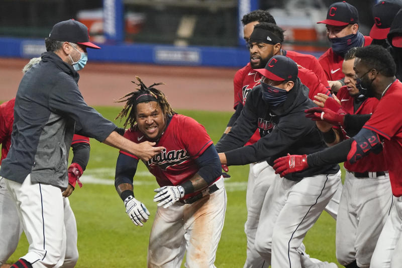 Cleveland Indians' Jose Ramirez, center, is mobbed after Ramirez hit a three-run home run in the tenth inning of a baseball game against the Chicago White Sox, Tuesday, Sept. 22, 2020, in Cleveland. (AP Photo/Tony Dejak)