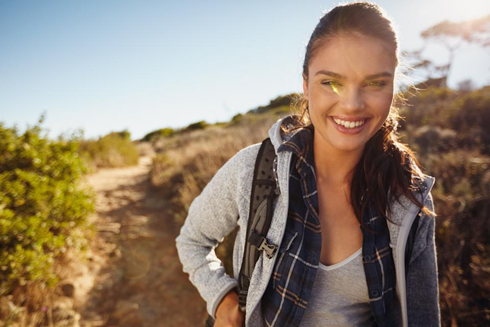 Hiker hiking in nature. Young woman smiling during hike. Caucasian female model outdoors on hike looking at camera. Enjoying summer vacation in countryside.