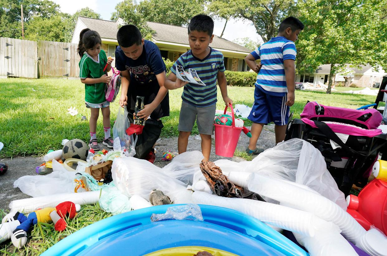 Children pick through toys in a trash pile on Sept. 2.