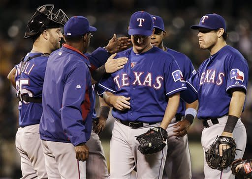 Texas Ranger's Roy Oswalt, center, is removed from the baseball game against the Oakland Athletics in the seventh inning by manager Ron Washington, Tuesday, July 17, 2012, in Oakland, Calif. (AP Photo/Ben Margot)