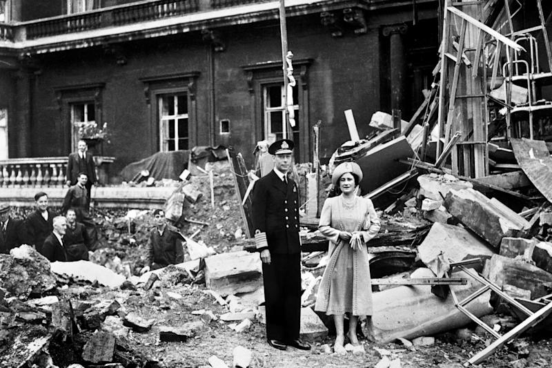 King George VI and the Queen Mother standing amid the bomb damage at Buckingham Palace (PA)