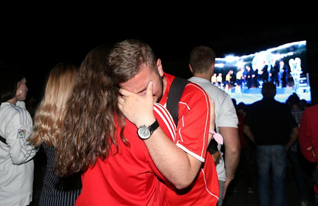 Soccer Football - Champions League Final - Real Madrid v Liverpool - Kiev, Ukraine - May 26, 2018 Liverpool fans look dejected after watching the match on a television screen outside the stadium REUTERS/Viacheslav Ratynskyi