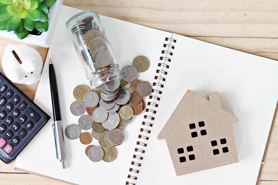 Business, finance, savings, property ladder or mortgage loan concept : Flat lay or top view of wood house model and coins scattered from glass jar on open blank notebook paper