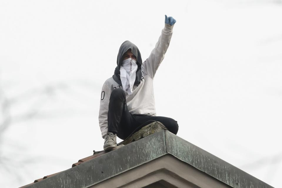 A man stands on the roof of the San Vittore prison during a protest in Milan, Italy, Monday, March 9, 2020. Italian penitentiary police say six inmates protesting virus containment measures at a northern Italian prison have died after they broke into the infirmary and overdosed on methadone. The protest Sunday in Modena was among the first of more than two-dozen riots at Italy's overcrowded lock-ups that grew Monday. Human rights advocates have been warning that increasing tensions over fears of coronavirus were hitting inmates particularly hard, especially after restrictions were imposed on family visits to prevent transmissions. (AP Photo/Antonio Calanni)