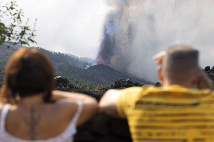 People watch as lava flows from an eruption of a volcano near El Paso on the island of La Palma in the Canaries, Spain, of Monday, Sept. 20, 2021. Lava continues to flow slowly from a volcano that erupted in Spain's Canary Islands off northwest Africa. The head of the islands' regional government says Monday he expects no injuries to people in the area after some 5,000 were evacuated. (AP Photo/Gerardo Ojeda)