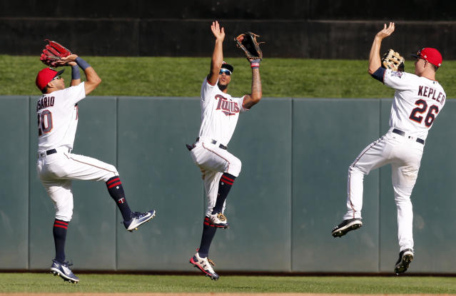 Minnesota Twins outfielders Eddie Rosario, left, Byron Buxton and Max Kepler, right, show their basketball 3-point form after the Twins beat the Toronto Blue Jays 13-7 on Sunday. (AP)