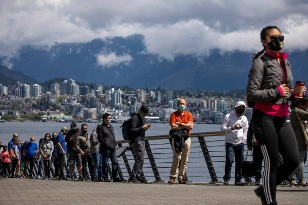 Essential workers line up outside the Vancouver Convention Centre during a COVID-19 vaccination clinic on May 7.  (Ben Nelms/CBC - image credit)