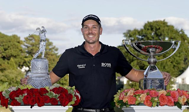 Henrik Stenson, of Sweden, poses with the trophies after winning the Tour Championship golf tournament and FedEx Cup at East Lake Golf Club, in Atlanta, Sunday, Sept. 22, 2013. (AP Photo/John Bazemore)