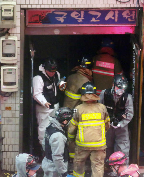 South Korean firefighters and police officers work at the gate of a fire site in Seoul, South Korea, Friday, Nov. 9, 2018. A fire at a low-cost dormitory-style housing facility in central Seoul killed several people on Friday, fire authorities said. (Hong Hae-in/Yonhap via AP)