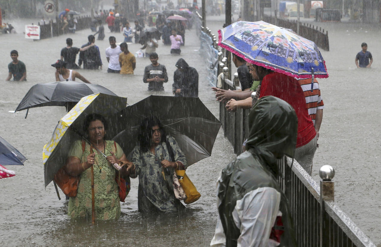 People navigate their way through a street flooded by torrential rains in Mumbai, India, on Sept. 4, 2019. (AP Photo/Rajanish Kakade)