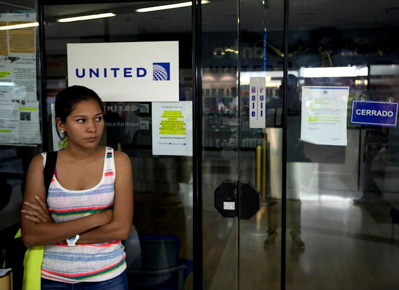 A woman stands outside a closed United Airlines office in Caracas, Venezuela, Friday, Jan. 24, 2014. Delta, American Airlines and Panama's Copa Airlines were also among carriers whose offices were either closed or had halted sales on Friday after the government devalued the local currency for flights abroad. (AP Photo/Alejandro Cegarra)