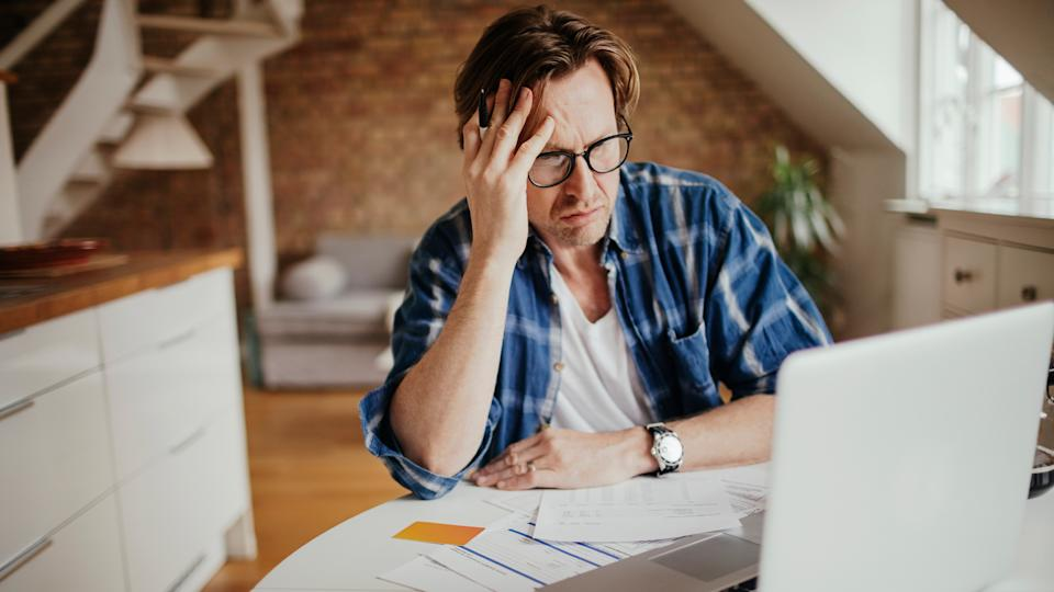 middle aged man looking frustrated with computer