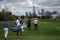 Jon Rahm, of Spain, center left, and Harris English, right, walk up the 10th fairway as the Manhattan skyline looms in the distance in the first round of play at the Northern Trust golf tournament, Thursday, Aug. 19, 2021, at Liberty National Golf Course in Jersey City, N.J. (AP Photo/John Minchillo)