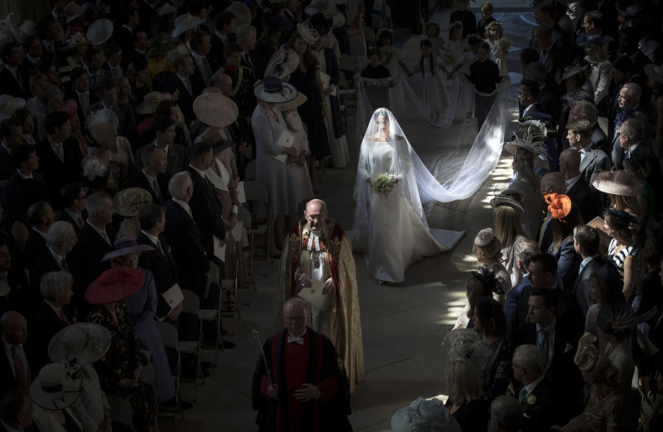 <p>Meghan walks down the aisle on her wedding day. Father-in-law Prince Charles accompanied her halfway (Getty) </p>