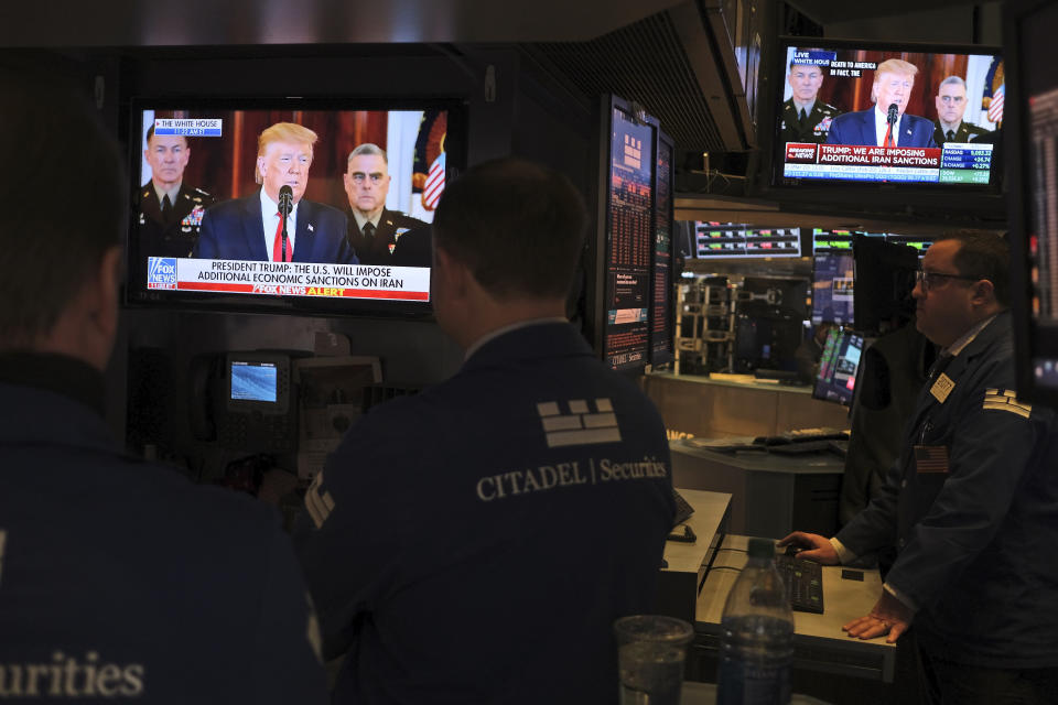 Traders pause to watch a televised speech by President Donald Trump as they work the floor of the New York Stock Exchange in New York, Wednesday, Jan. 8, 2020. (AP Photo/Seth Wenig)