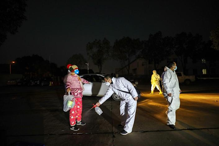 A man disinfects a woman arriving at a hotel accommodating isolated people in Wuhan on February 3, 2020.