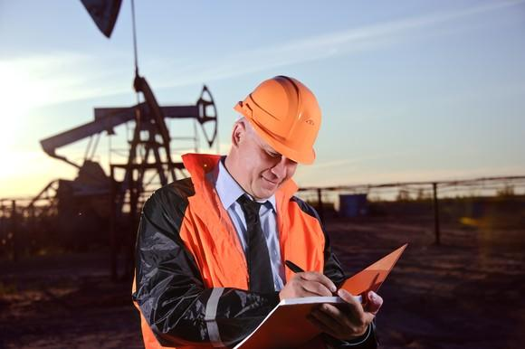 A man wearing an orange hard hat and jacket writing in a notebook with an oil well behind him.