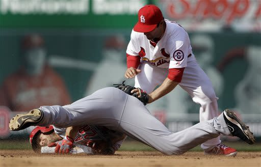 Cincinnati Reds' Chris Heisey, bottom, is safe at second for a double ahead of the tag from St. Louis Cardinals shortstop Pete Kozma during the fourth inning of a baseball game, Monday, April 8, 2013, in St. Louis. (AP Photo/Jeff Roberson)