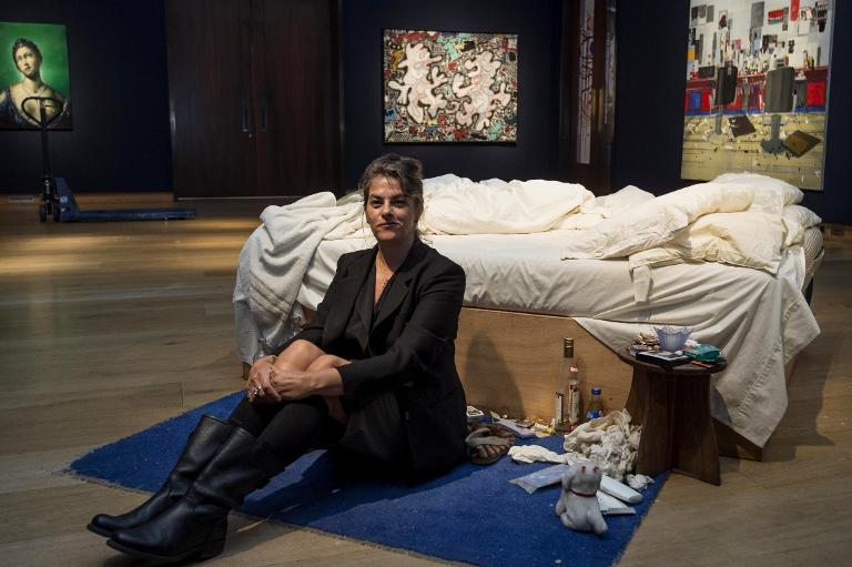 "British artist Tracey Emin sits on her iconic art installation, ""My Bed"", during a press preview at Christie's auction house in London on June 27, 2014"