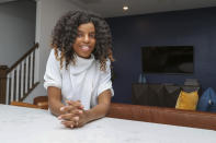 Crystal Marie McDaniels poses at the bar in her kitchen of her home in Charlotte, N.C., on Friday, July 9, 2021. Mcdaniels said buying a house was crucial for her because she wants to pass on wealth to her son someday, giving him an advantage she never had. So when the loan officer told her the deal wasn't going to happen, she refused to give up. (AP Photo/Nell Redmond)
