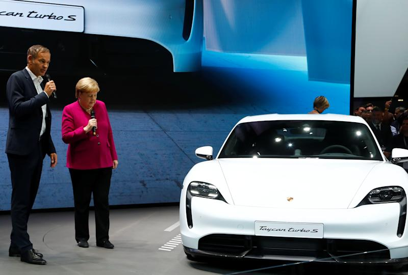 Porsche AG CEO Oliver Blume and German Chancellor Angela Merkel speak next to Porsche Taycan Turbo S at the international Frankfurt Motor Show IAA in Frankfurt, Germany September 12, 2019. REUTERS/Ralph Orlowski