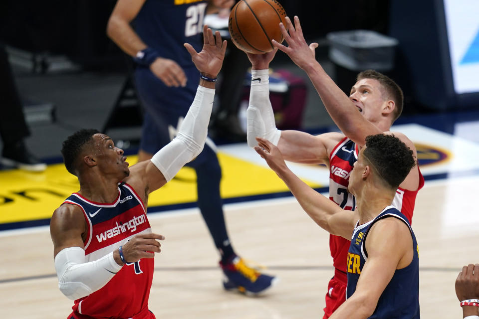 Washington Wizards' Moritz Wagner (21) and Russell Westbrook (4) and Denver Nuggets forward Michael Porter Jr. (1) go after a rebound during the first quarter of an NBA basketball game Thursday, Feb. 25, 2021, in Denver. (AP Photo/Jack Dempsey)