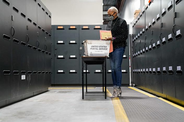 An election worker validates ballots at the Gwinnett County elections office in Lawrenceville, Ga.