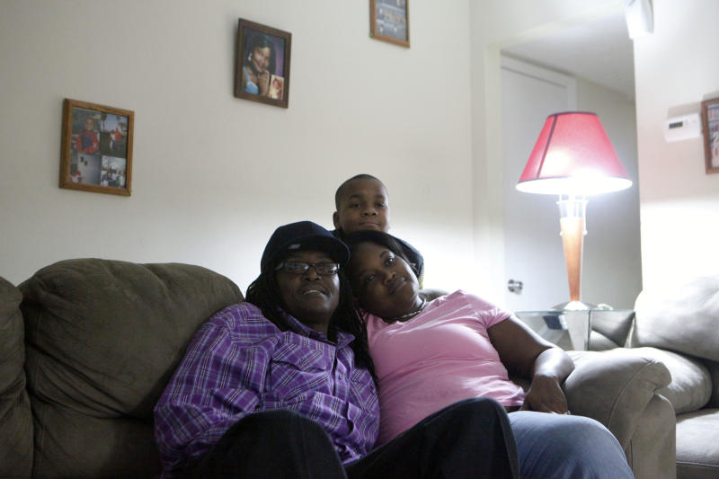 """Veteran Larry Mainor, 48, left, who was homeless for nearly 30 years, watches a football game on T.V. with his fiancé Naketta Virella and her 11-year-old son TaDarios Virella in Mainor's home, Saturday, Aug. 17, 2013, in Decatur, Ga. Atlanta's """"Unsheltered No More"""" initiative is currently working to place homeless veterans and the chronically homeless, like Mainor, into permanent housing. The city is on-track to end chronic and veteran homelessness by 2015. (AP Photo/Jaime Henry-White)"""