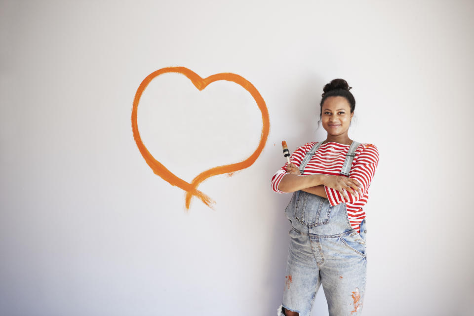 Portrait of confident pregnant woman standing by heart shape painted on wall