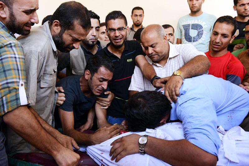 Family and friends mourn over the body of a Palestinian translator, Ali Abu Afash, who was killed in Beit Lahia in the northern Gaza strip on August 13, 2014 (AFP Photo/Roberto Schmidt)