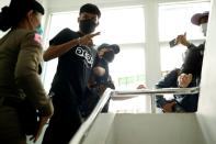 Panupong Jadnok, a pro-democracy student, one of the leaders of Thailand's recent anti-government protests, is escorted after being arrested, at the police station in Bangkok