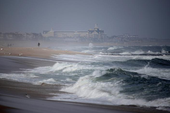 A beachgoer walks along the water as waves crash in Manasquan, N.J. A large system of ocean currents in the Atlantic – which includes the Gulf Stream – has been disrupted due to human-caused climate change, scientists reported in a new study published Thursday.