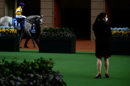 A Hong Kong Jockey Club employee wears a face mask in the parade ring at an empty Sha Tin racecourse on Hong Kong Gold Cup day
