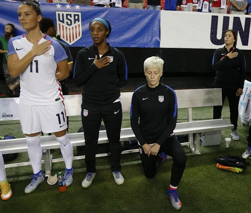 Megan Rapinoe kneels next to teammates Ali Krieger and Crystal Dunn as the US national anthem is played before a match against Netherlands in Atlanta in 2016.